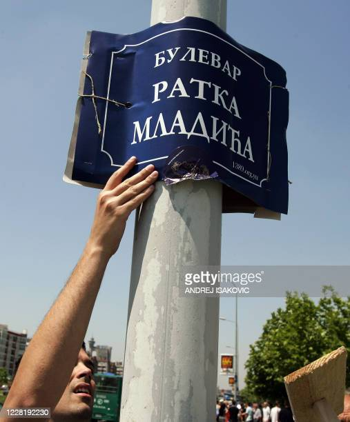 """Supporter of Ratko Mladic attaches on a lamppost poster bearing the name """"Ratko Mladic Boulevard"""" in Belgrade, 26 May 2007. A few hundred..."""