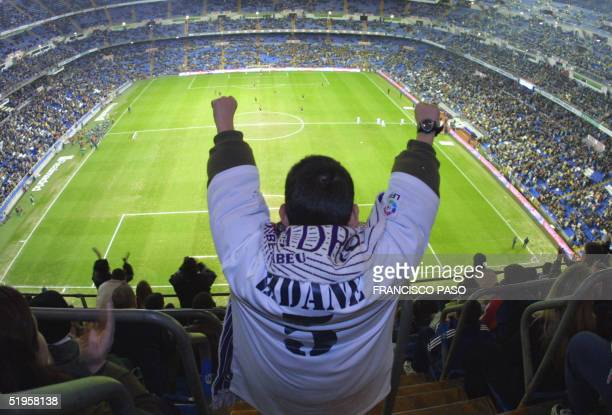 Supporter of Real Madrid wearing the jersey of French star Zinedine Zidane raises his arms at the beginning of the quarterfinal match of the Copa del...