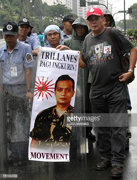 A supporter of rebel Senator Antonio Trillanes displays his portrait in front of riot police outside the luxury Peninsula hotel in Manila's financial...