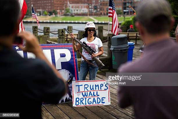 A supporter of Republican Presidential candidate Donald Trump pose with a riffle at an 'America First' unity rally July 18 2016 in Cleveland Ohio