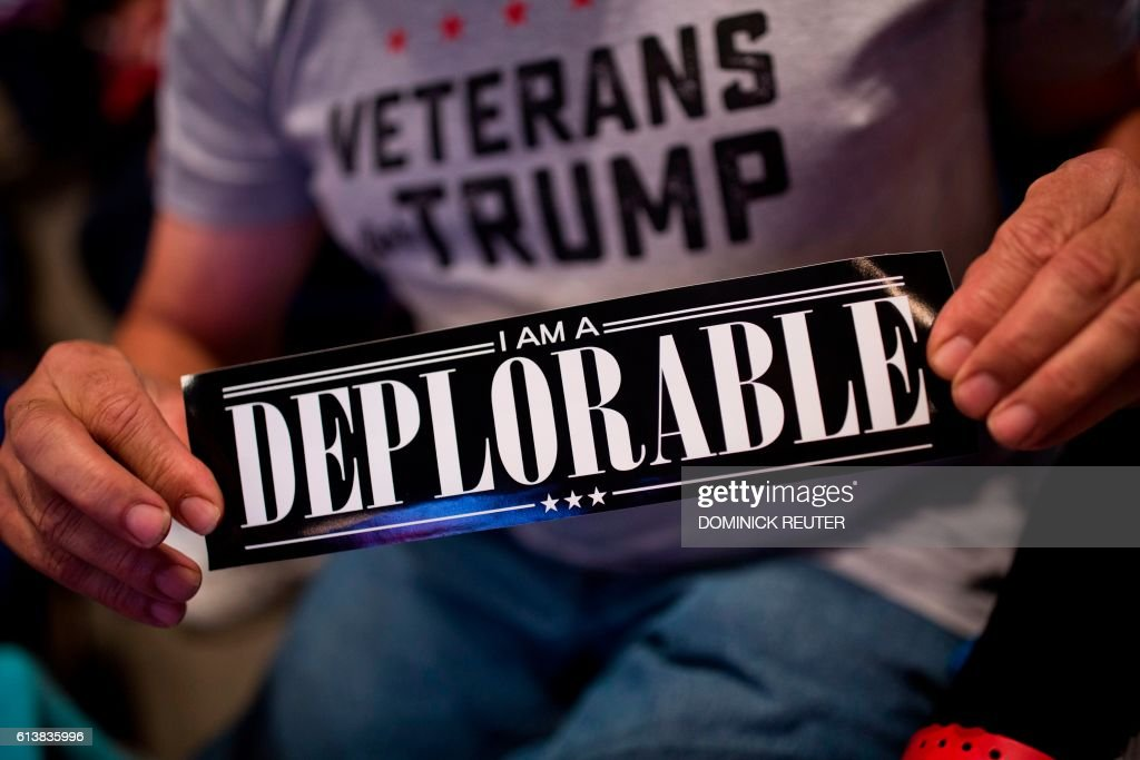 TOPSHOT - A supporter of Republican presidential candidate Donald Trump shows a bumper sticker reading 'I am a Deplorable' at Mohegan Sun Arena in Wilkes-Barre, Pennsylvania on October 10, 2016. /