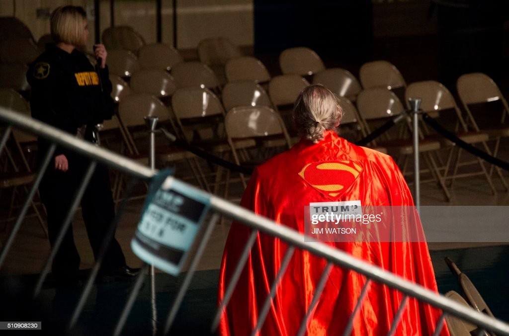 A supporter of Republican presidential candidate Donald Trump wearing a Superman cape departs the Civic Center after a campaign rally in Sumter, South Carolina, February 17, 2016. / AFP / JIM