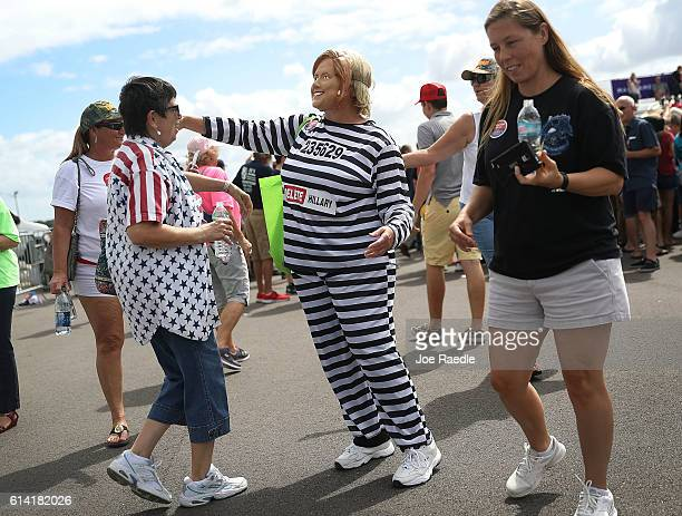 A supporter of Republican presidential candidate Donald Trump wears a Hillary Clinton in prison garb custom as people wait at his campaign rally at...