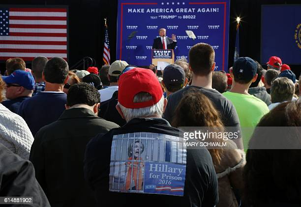 TOPSHOT A supporter of Republican presidential candidate Donald Trump wears a shirt that reads Hillary for Prison as Trump speaks at an event on...