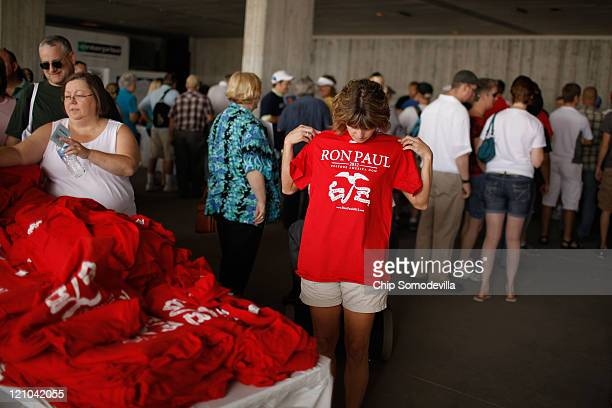 A supporter of Republican presidential candidate Rep Ron Paul checks a free tshirt for size outside the Hilton Coliseum where Iowans will vote in the...
