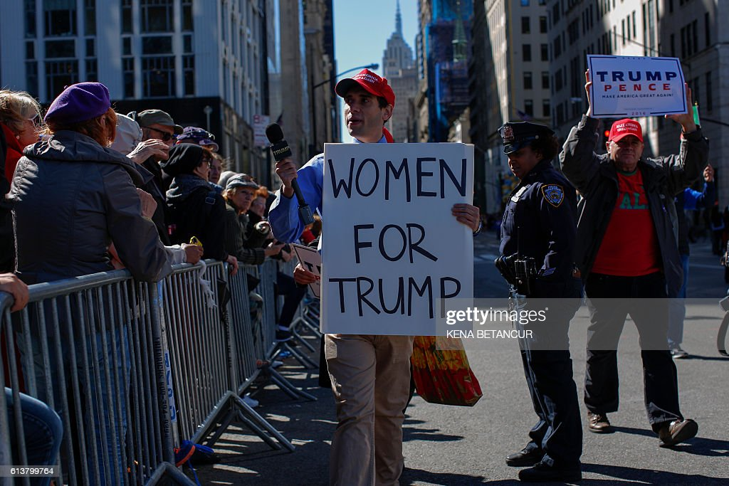 A supporter of Republican presidential nominee Donald Trump holds a placard as he attends the annual Columbus day parade in New York on October 10, 2016. / AFP / KENA