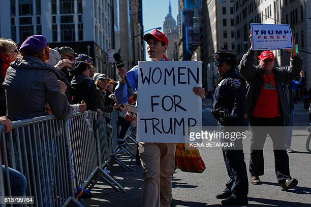 A supporter of Republican presidential nominee Donald Trump holds a placard as he attends the annual Columbus day parade in New York on October 10...