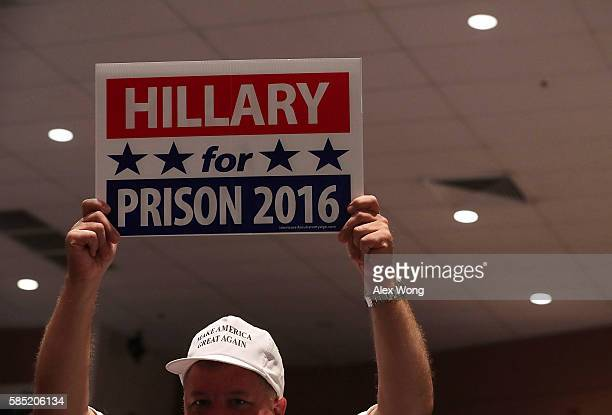 A supporter of Republican presidential nominee Donald Trump holds up a Hillary for Prison 2016 sign during a campaign event at Briar Woods High...