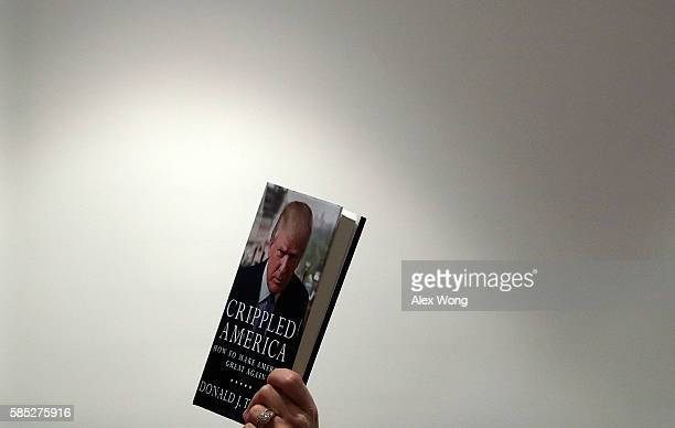 """Supporter of Republican presidential nominee Donald Trump holds up a copy of his book """"Crippled America: How to Make America Great Again"""" during a..."""