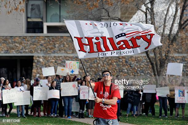 A supporter of Republican presidential nominee Donald Trump waves an antiClinton flag as proClinton supporters demonstrate behind him outside the the...
