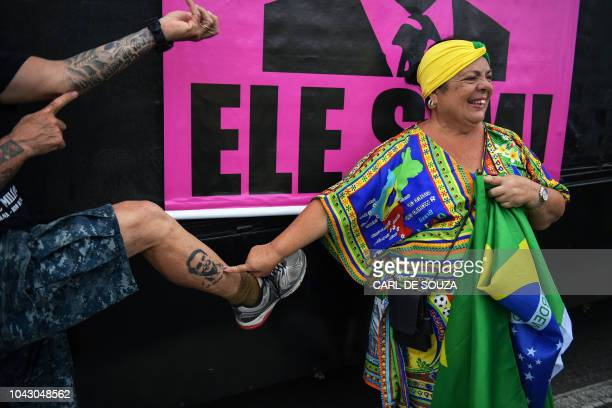 A supporter of rightwing presidential candidate Jair Bolsonaro points at a man's tattooed leg with the portrait of Bolsonaro during the 'Women for...