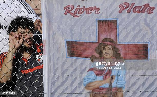 A supporter of River Plate cheers for his team nex to a flag with an image of Gauchito Gil legendary gaucho saint of the popular culture of Argentina...