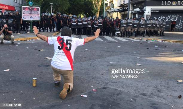 TOPSHOT A supporter of River Plate gestures at riot police in the surroundings of the Monumental stadium in Buenos Aires following an attack on the...