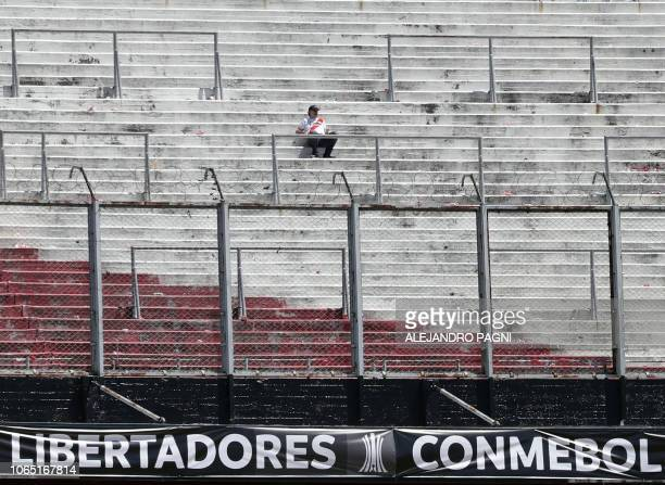 Supporter of River Plate sits on an empty stand at the Monumental stadium in Buenos Aires, after the all-Argentine Copa Libertadores second leg final...