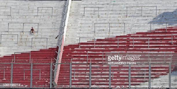 TOPSHOT A supporter of River Plate sits on an empty stand at the Monumental stadium in Buenos Aires after the allArgentine Copa Libertadores second...