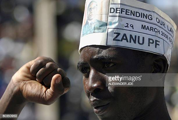 A supporter of Robert Mugabe leader of Zimbabwe's ruling National Africa Union Patriotic Front raises a clinched fist as Mugabe addresses a rally in...
