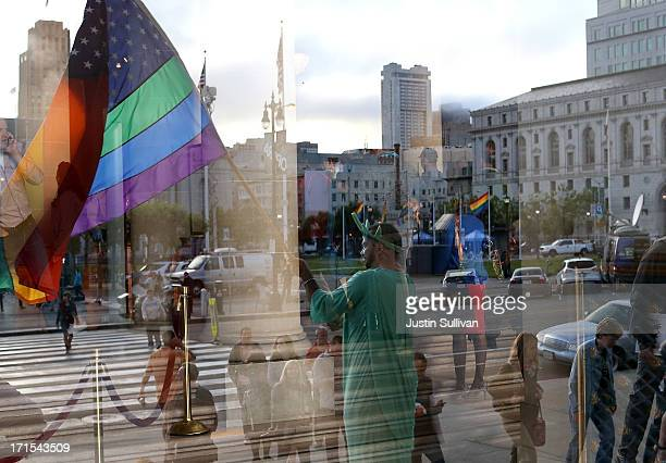 A supporter of samesex marriage waves a pride flag in front of San Francisco City Hall before the announcement of the results of the US Supreme...