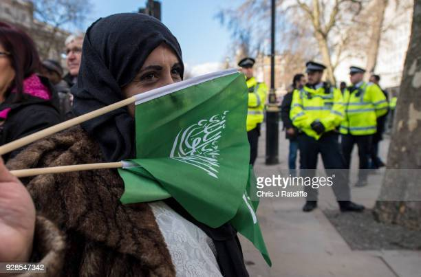 A supporter of Saudi Crown Prince Mohammed bin Salman holds flags of Saudi Arabia in front of her face opposite Downing Street as the Crown Prince...