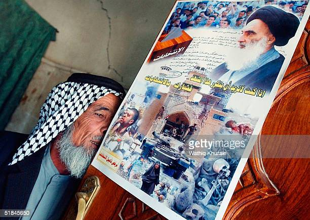 Supporter of Shiite cleric Ayatollah al-Sistani kisses the gate of Buratha mosque as a poster urging for participating in the coming elections is...
