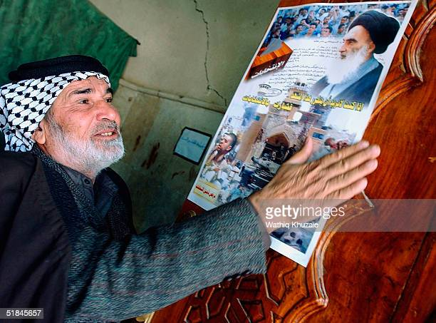 Supporter of Shiite cleric Ayatollah al-Sistani makes blessings as a poster urging for participation in the coming elections is seen inside the...