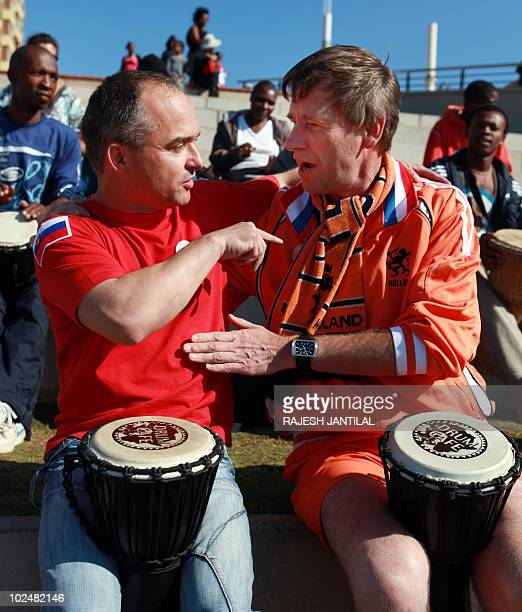 A supporter of Slovakia's football team and one of the Netherland's exchange views as they play drums along Durban's North Pier Beach prior to the...