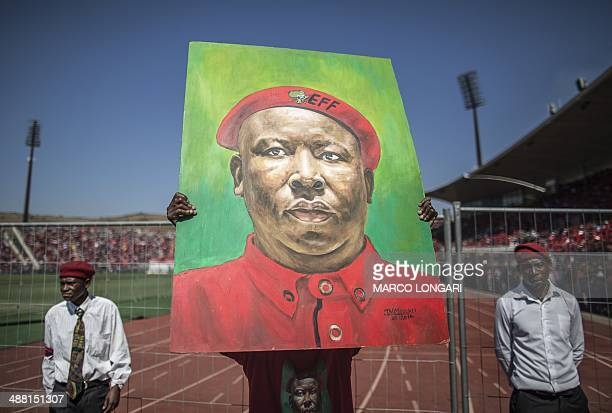 A supporter of South Africa's Economic Freedom Fighters party holds up a portrait of party leader Julius Malema during the final EFF electoral...
