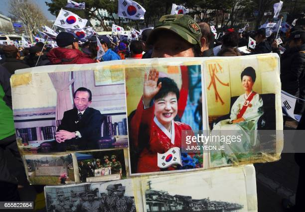 A Supporter of South Korea's impeached expresident Park GeunHye holds portraits of Park GeunHye her father former dictator Park ChungHee and her...