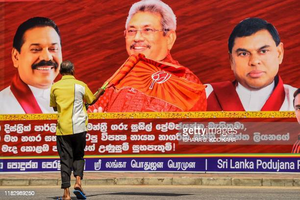 A supporter of Sri Lanka Podujana Peramuna party presidential candidate Gotabaya Rajapaksa waving a flag walks past a cutout placard of the Rajapaksa...