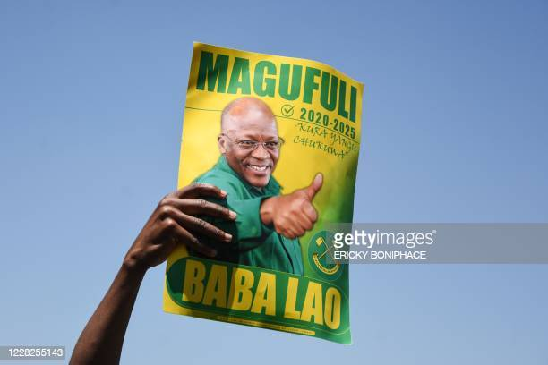 Supporter of Tanzania's ruling party Chama Cha Mapinduzi holds a sign during the official launch of the party's campaign for the October general...