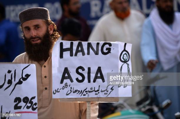 A supporter of TehreekeLabaik Pakistan a hardline religious political party holds a placard during a protest in Rawalpindi on October 12 demanding...