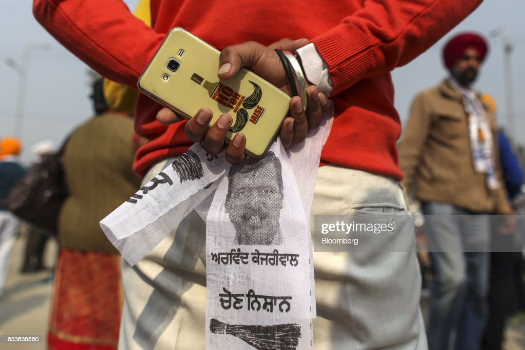 A supporter of the Aam Aadmi Party holds a mobile phone and a scarf featuring an image of Arvind Kejriwal leader of the AAP and chief minister of...