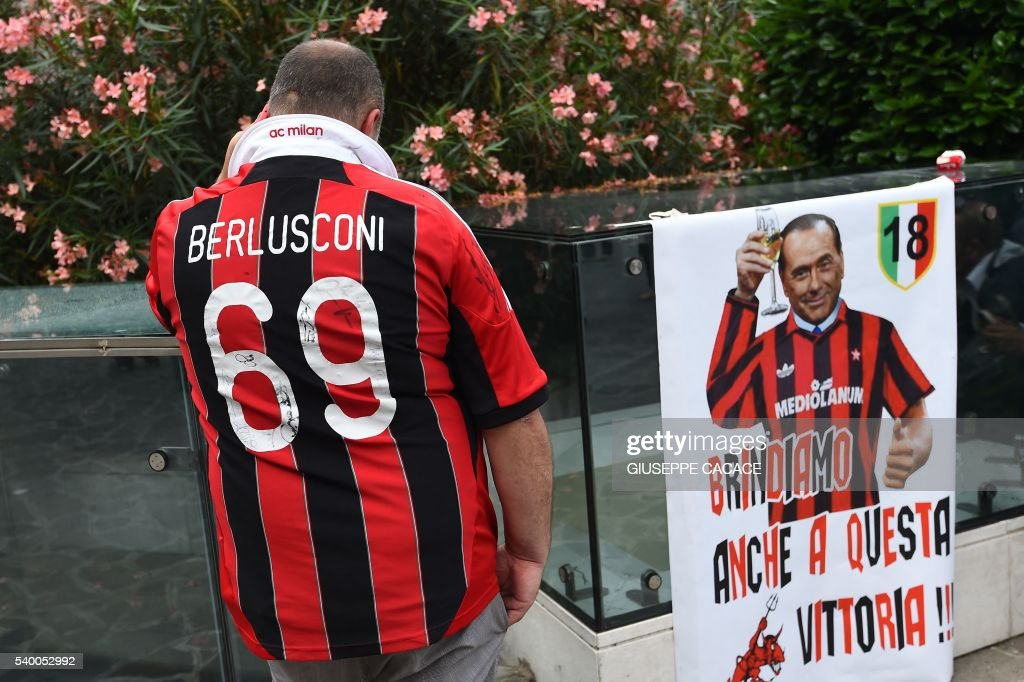 A supporter of the AC Milan football club wears a jersey of the honorary president of the club Silvio Berlusconi, as he waits outside the San Raffaele hospital on June 14, 2016 in Milan. Italian former Prime Minister Silvio Berlusconi was undergoing cardiac surgery on Tuesday after a heart attack his doctor said could have killed the 79-year-old tycoon. 'At 8:00am (0600 GMT) this morning, the operation to replace his aortic valve began,' the San Raffaele hospital in Milan said in a statement. The surgery is expected to last for four hours and Berlusconi will be in intensive care for another two days, the hospital said. CACACE
