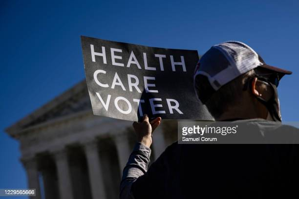 A supporter of the Affordable Care Act stands in front of the Supreme Court of the United States as the Court begins hearing arguments from...
