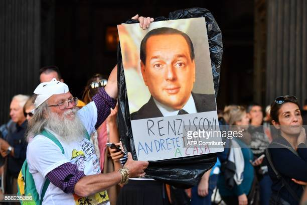 A supporter of the antiestablishment Five Star Movement holds a poster reading 'Renzusconi you will all go home' and showing a photomontage of the...