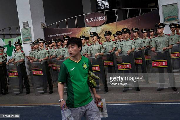 A supporter of the Beijing Guoan FC walks passed police officers before the team's match against Chongcing Lifan FC in Chinese Super League play on...