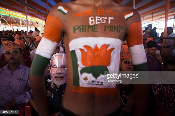 A supporter of the Bharatiya Janata Party second left wears a mask of Indian Prime Minister Narendra Modi during a rally in Muzaffarpur Bihar India...