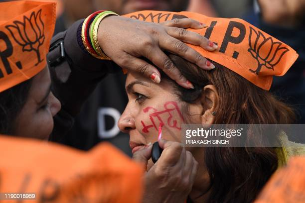 A supporter of the Bharatiya Janata Party writes Modi on the cheek of another supporter as they await the arrival of India's Prime Minister Narendra...