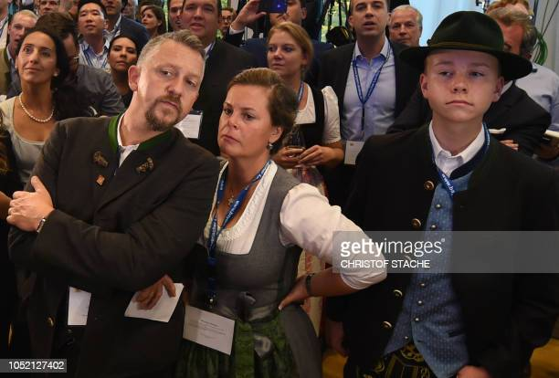 TOPSHOT Supporter of the Christian Social Union react after first exit polls were announced on public television at the Bavarian regional government...