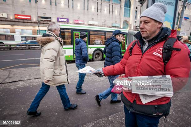 Supporter of the Communist Party gives pamphlets in the streets of Moscow Russia on 14 March 2018 during the presidential campaign of Russia 2018