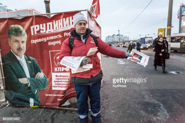 Supporter of the Communist Party gives pamphlets of the official candidate Pavel Grudini in the streets of Moscow Russia on 14 March 2018 during the...