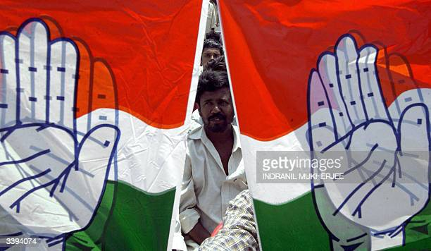 A supporter of the Congress party is framed between party symbols during a rally of Indian Opposition Leader and Congress Party President Sonia...