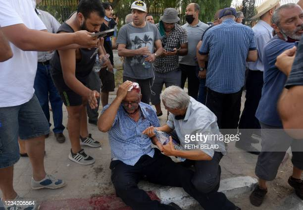 Supporter of the country's Islamist Ennahda party is injured by a stone thrown at him during a protest outside the parliament building in the capital...