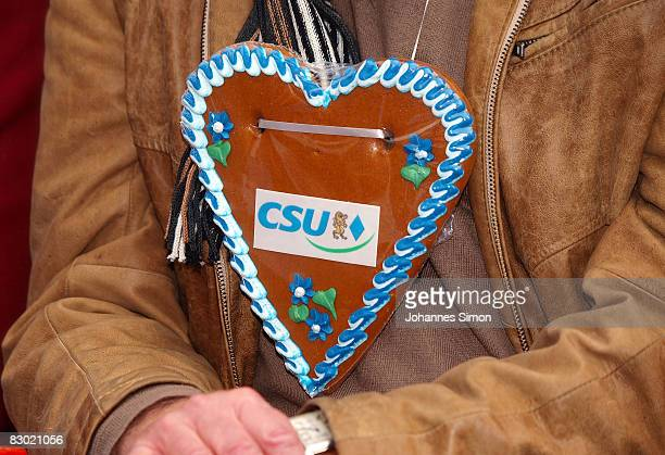 A supporter of the CSU wears a gingerbread heart displaying 'CSU' during a final campaign rally of the Christian Social Union in front of the Munich...