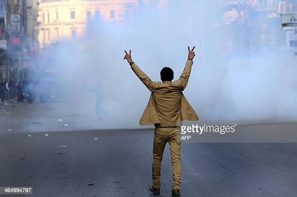 A supporter of the Egyptian government flashes the sign for victory during clashes with Muslim Brotherhood supporters in Cairo on January 25 2014...