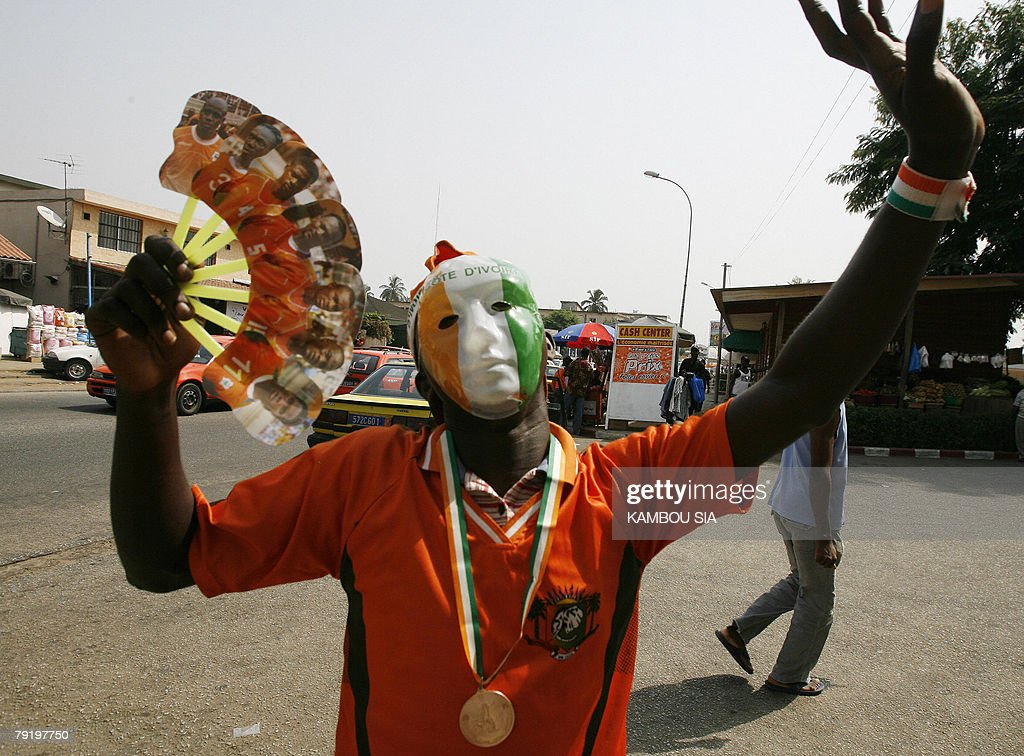 A supporter of the Elephants, the Ivorian national football team, wearing a mask with the Ivorian colours, waves a fan with portraits of the players 24 January 2008 in Abidjan. Ghana's Michael Essien is relishing the prospect of coming up against his Chelsea teammate Didier Drogba's Ivory Coast in the African Nations Cup final.