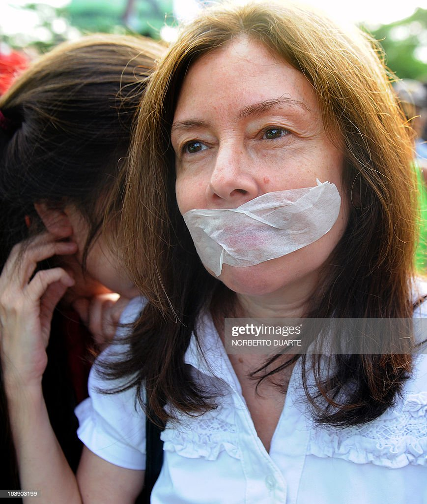 A supporter of the Frente Guasu party, whose presidential candidate Anibal Carrillo was not invited by a private firm to take part in a televised presidential debate, tapes her mouth during a protest on March 17, 2013 in Asuncion. Paraguay will hold presidential elections next April 21. AFP PHOTO/Norberto Duarte