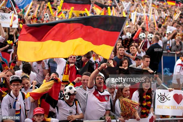 A supporter of the german team waves a german flag surrounded by german fans celebrating while they watch the FIFA World Cup 2014 group G football...