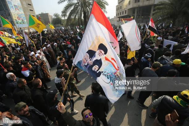 A supporter of the Hashed alShaabi paramilitary waves a flag bearingimages of Iran's Supreme Leader Ayatollah Ali Khamenei the late Iranian military...