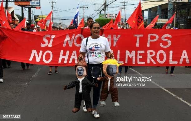 A supporter of the Honduran Opposition Alliance Against the Dictatorship and LIBRE party prepares to set fire two dummies depicting US President...