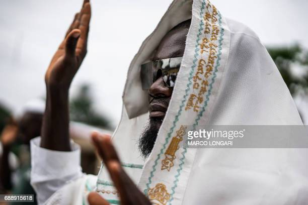 A supporter of the Indigenous People of Biafra covers his head with a prayer shawl as he joins members of the Yahveh Yashua Synagogue celebrating...